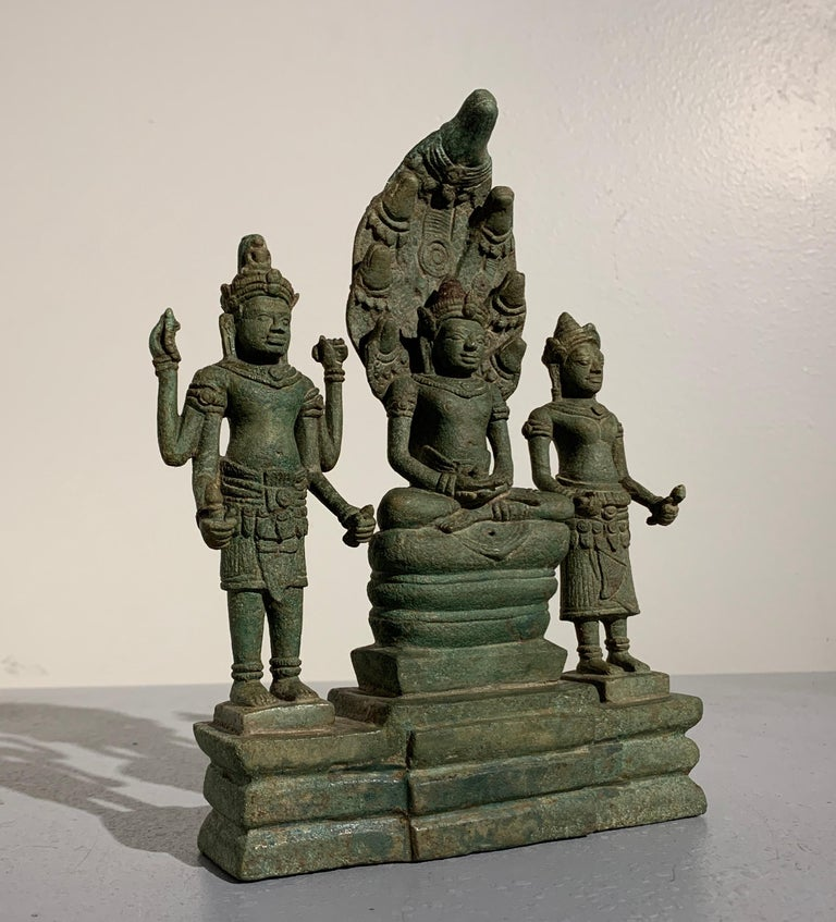 An important Khmer bronze Buddhist triad group featuring an image of the Buddha sheltered by a Naga, and flanked by the bodhisattvas Avalokiteshvara and Prajnaparamita, Angkor Period, Style of the Bayon, late 12th-early 13th century, Cambodia.