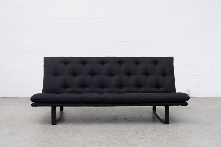 Amazing midcentury low, stealth and tufted 3-seat sofa designed by Kho Liang ie for Artifort, Holland. New black upholstery and original black enameled metal frame in original condition with some wear and scratching. Wear is consistent with it's age