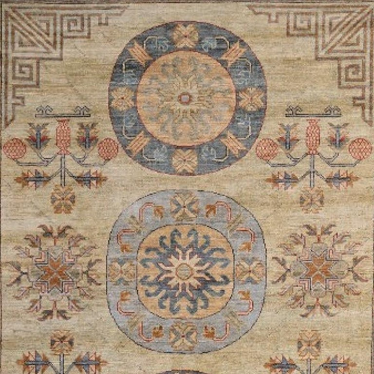 A medium sized rug with traditional Khotan design. The pile is made of high end quality wool - hand spun, hand dyed with all vegetable dyes and knotted by master weavers. The rug is very decorative and has a towards square format. The condition is