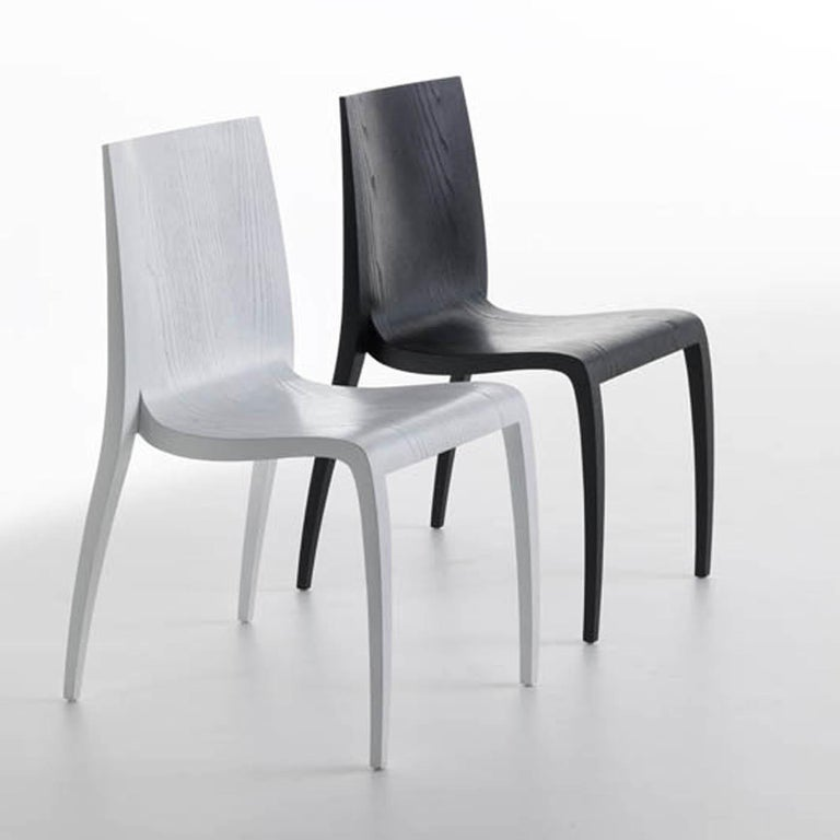 "Inspired by the Japanese concept of energy enclosed in the word ""ki"", Mario Bellini designed this exquisite contemporary chair boasting an elegant yet simple silhouette. Sinuous and lightweight, the legs are made of ash wood with an open-pore"