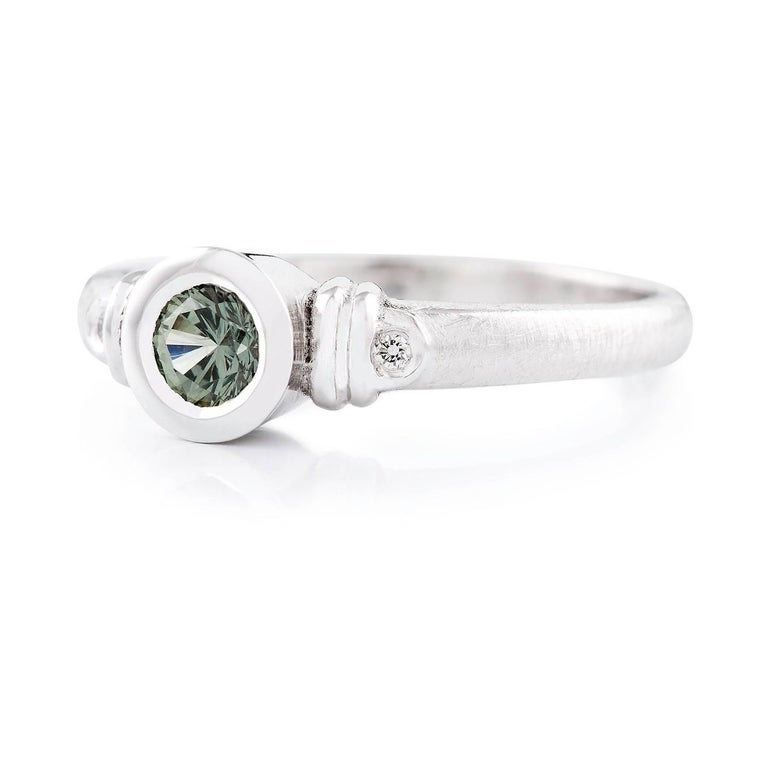 verde Zaffiro Ring  This gorgeous white gold dress ring features a stunning round green sapphire that is complimented with round brilliant ut diamonds on either side, all set in 18ct white gold. The band is made of 18ct white gold with an