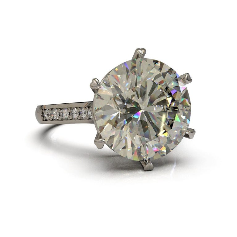 Equilateral Ring   Beautiful and understated, this ring is made in platinum with an attractive 6.01 carat fancy round brilliant cut diamond with the finest white shoulder diamonds.    Round brilliant cut diamond: 1=  M Color, VVS2- clarity, 6.01