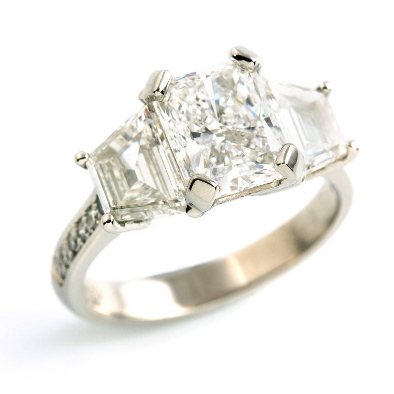 Platinum Diamond Ring  This breathtaking beauty is set with three of the finest quality diamonds. The platinum band is further bead set with twelve petite diamonds of similar fine quality.  Corner rectangular modified brilliant cut: GIA certified, D