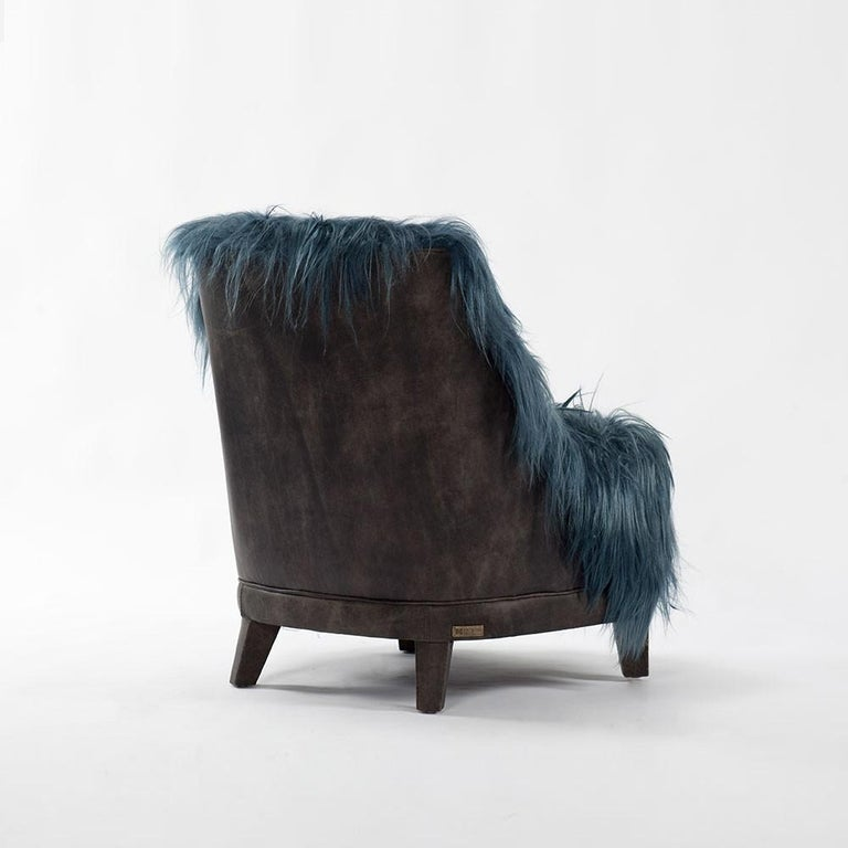 Contemporary club chair featuring natural Kidassia goat fur in petrol blue tone and high quality leather. Dimensions: H84 cm x W70 cm x D77 cm Materials: Natural goat fur, leather Color combination: Dark Beige, petrol blue.
