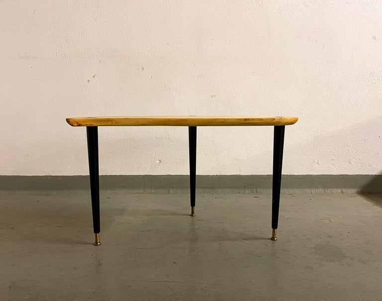 Nicely shaped organic formed side table in pine and brass with black lacquered legs. The legs with brass finish and the top with rounded brass details. Made in Sweden at Svensk Fur.   Good vintage condition with the surface of the table