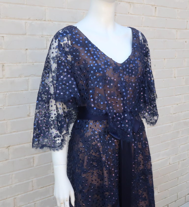Kiki Hart creates a beautiful dark blue lace formal dress with nude illusion panels and sequins for catching the evening light.  Though from the 1960's, the silhouette of the dress pays homage to Edwardian designs with a capelet style overlay at the