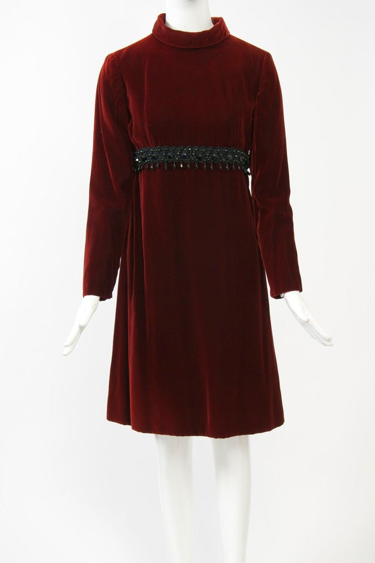 Rich burgundy velvet 1960s dress by Kiki Hart featuring an empire bustline trimmed with a band of black soutache and jet beads. A rolled turtleneck, narrow, set-in sleeves, and an A-line skirt complete the look. Fully lined. Back zipper. Approximate