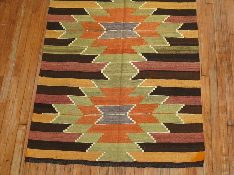 """A vintage Turkish Kilim wide runner with 5 green and orange medallions on a striped ground, circa mid 20th century. Measures: 3'10"""" x 10'10""""."""