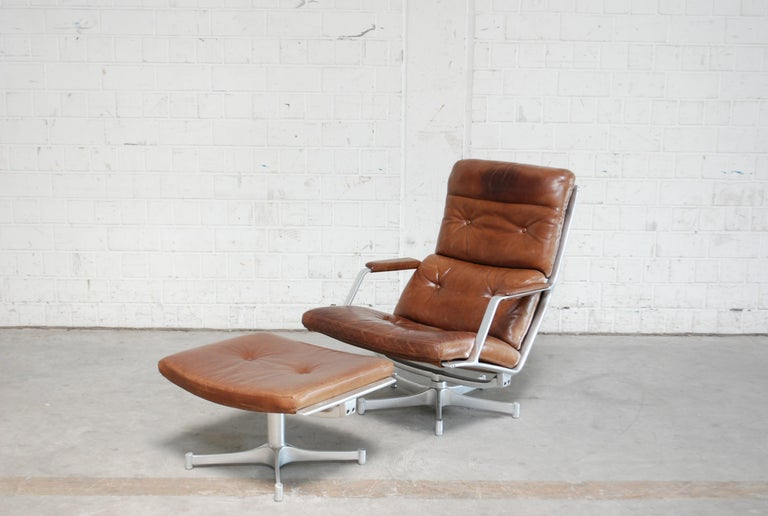 FK 85 was made by Jorgen Kastholm & Preben Fabricius for Kill international The lounge chair and ottoman has an swivel aluminium frame and cognac Leather. The leather has patina on the headrest. The colour is a brown cognac.