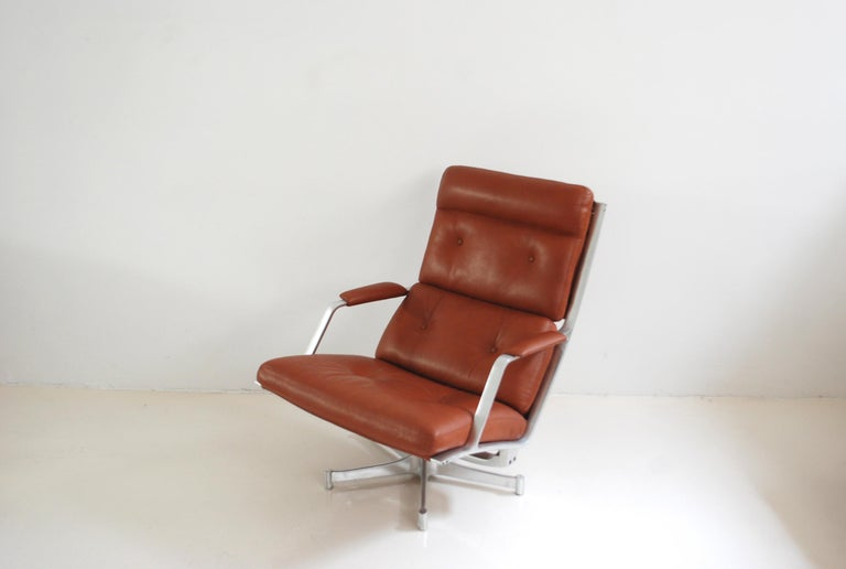This lounge chair FK 85 was made by Jorgen Kastholm & Preben Fabricius for Kill International. The lounge chair has a swivel aluminium frame and red cognac leather. It was new upholstered with aniline leather. The aluminium frame has some signs