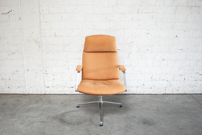 Thisoffice armchair FK 86 was made by Jorgen Kastholm & Preben Fabricius for kill international. It has a three-leg swivel aluminium base and a thick cognac leather with suede aniline grain.  We have 2 chairs in stock.