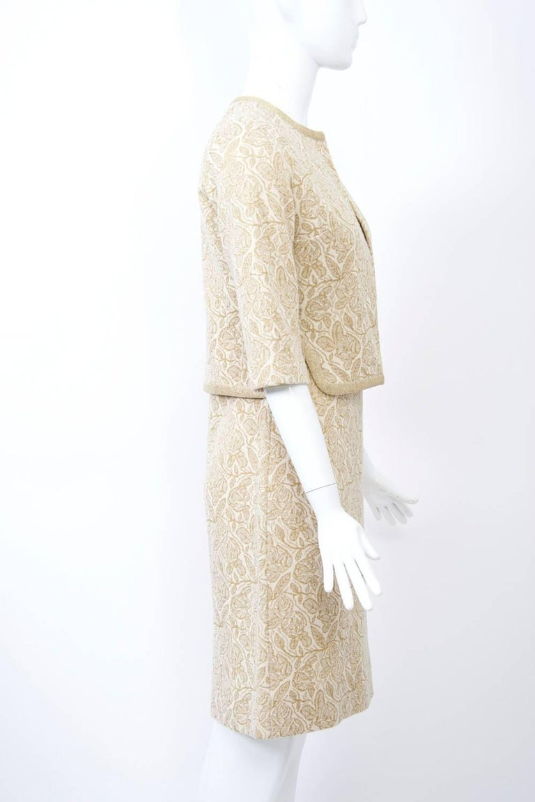 Kimberly was one of the best knitwear manufacturers in mid-century America. This ensemble, from the 1960s, consists of a sheath dress and short, open jacket of ivory ground with gold metallic weave in an abstract leaf pattern. The body hugging dress