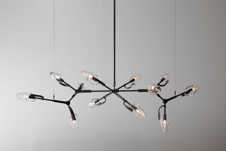 Kinesis chandelier is a modular lighting system featuring blown glass diffusers which are interconnected by solid brass components. The resulting fixture is a lithe and sculptural centerpiece, which is unique from every angle. This listing features