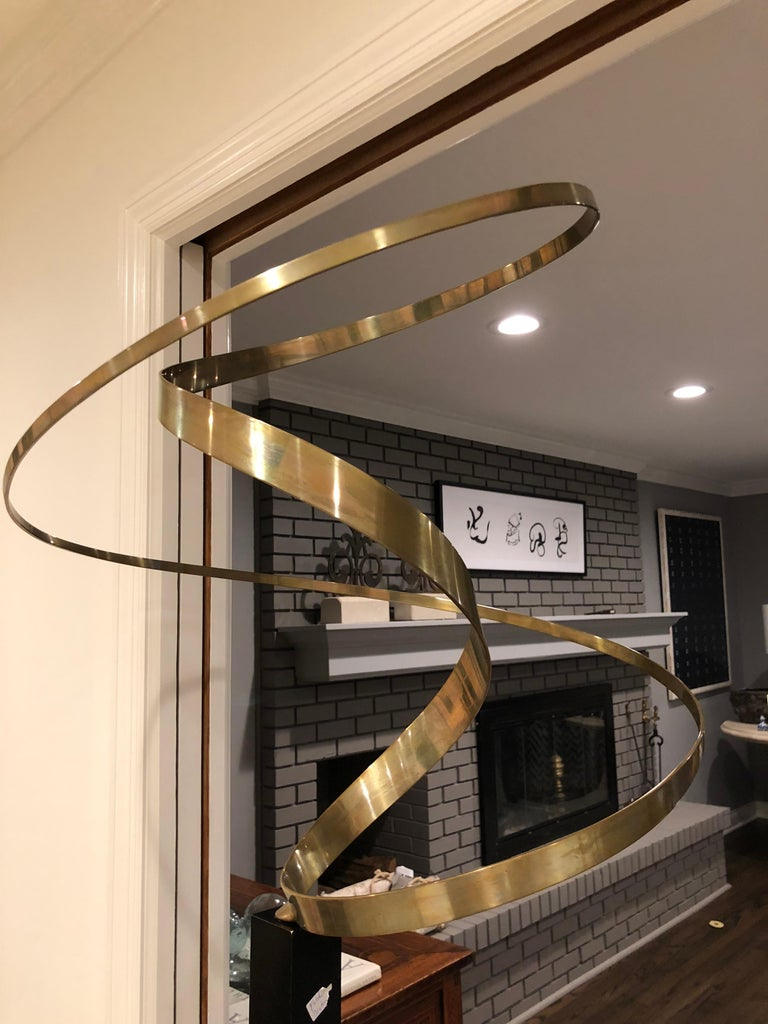An abstract large brass ribbon sculpture  having Kinetic capabilities when plugged in. (It does not have to be plugged in to appreciate its presence.) Housed in a black metal stand. Cord is at base.