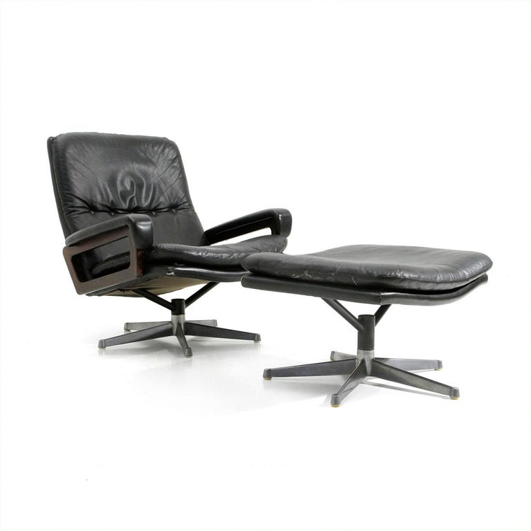 Armchair with ottoman produced in the 1960s by Strässle and designed by André Vandenbeuck. The armchair was distributed in Italy by Arflex. Aluminum base. Pivoting metal structure padded and lined in black leather. Armrests in wood with padded