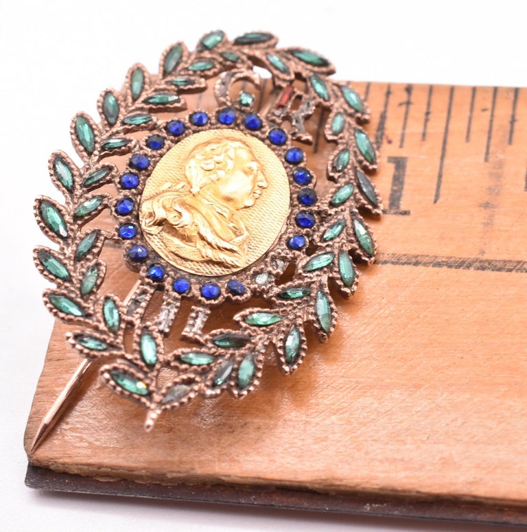 Rarely seen George III commemorative brooch with George III in profile at the center adorned with a border of blue and green Vauxhall glass. This historical brooch was thought to have been made to celebrate George III's recovery from porphyria in