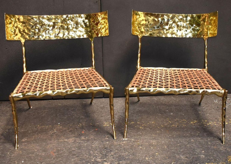 Two solid brass curve low back slipper chairs with leather strapping and crystal coating finish. (No cushion)  Dimensions: King chair width curve back 28 inches Width seat 24 inches Depth 23 inches Height seat without cushion 13