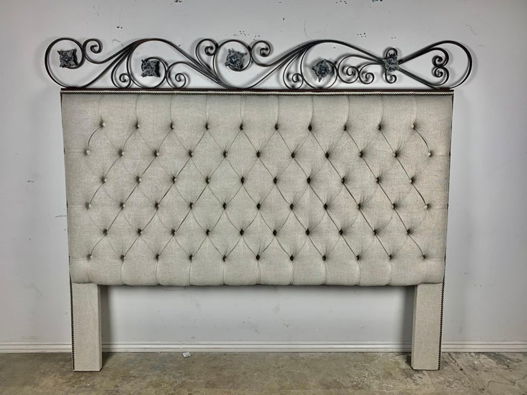 Custom King size Belgium linen tufted headboard. The headboard is crowned with beautiful scrolled ironwork depicting flowers. Antique brass nailhead trim detail.