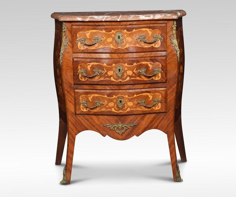 Kingwood and marquetry commode, in Louis XVI transitional style, of serpentine bombe form, fitted three drawers above a shaped apron and tall angular splayed legs, inlaid with panels of flower sprays, swags and pendants, gilt brass foliate handles,