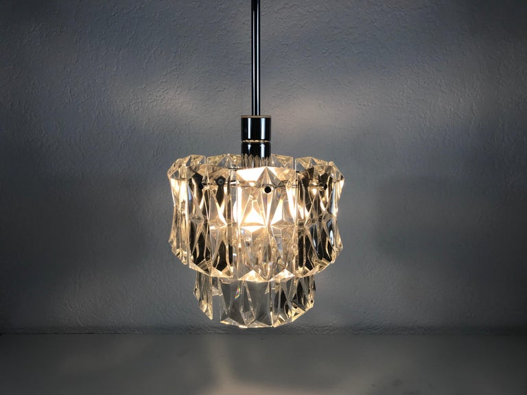 A Kinkeldey ice glass chandelier made in Germany in the 1960s. It is fascinating with its rare glass shapes. Modernist design chandelier with two circular tiers. It has a chrome metal frame.  Measurements:  Height 50 cm  Diameter 24 cm  The