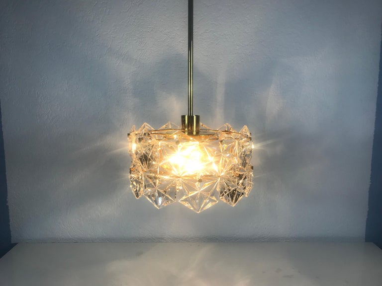 A Kinkeldey ice glass chandelier made in Germany in the 1960s. It is fascinating with its beautiful hexagonal shape of the crystal glass. All metal parts of this light are gold plated and in a very high quality standard. The crystals are all hand