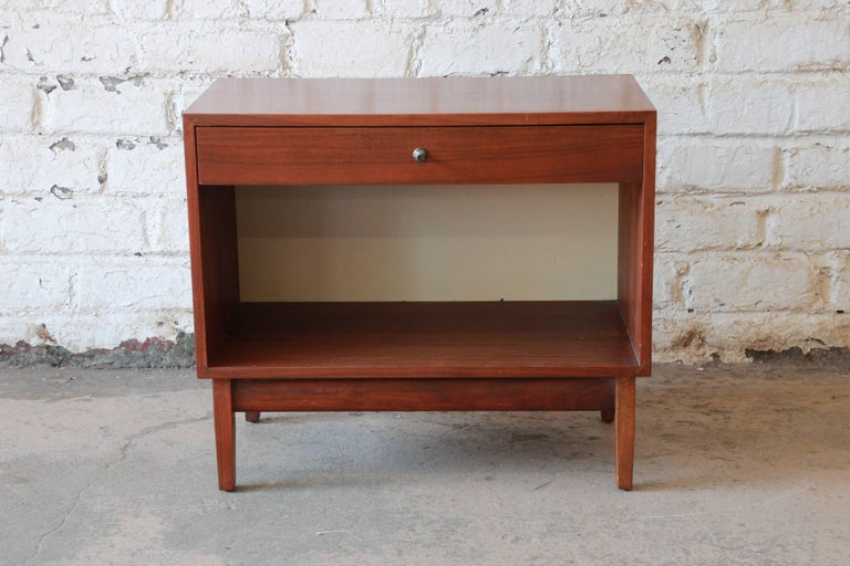 An outstanding Mid-Century Modern walnut nightstand designed by Kipp Stewart for his American Design Foundation line for Calvin Furniture, circa 1950s. The nightstand features gorgeous walnut wood grain and sleek mid-century design. It offers good