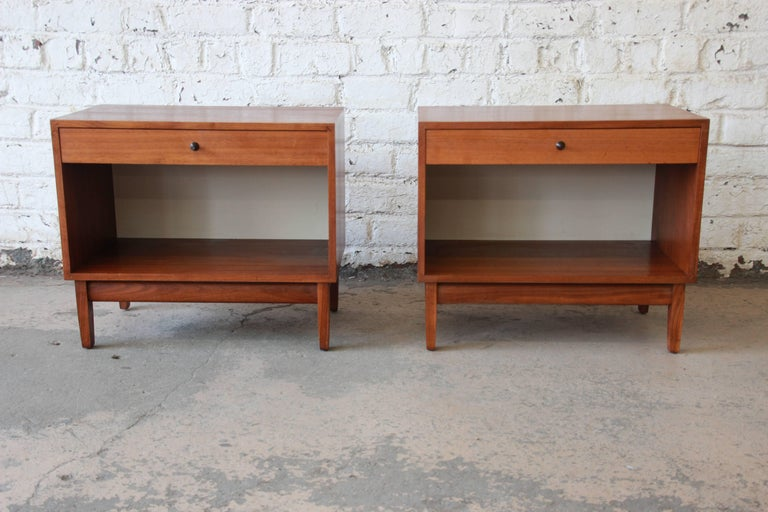 An outstanding pair of Mid-Century Modern walnut nightstands designed by Kipp Stewart for his American Design Foundation line for Calvin Furniture, circa 1950s. The nightstands feature gorgeous walnut wood grain and sleek mid-century design. They