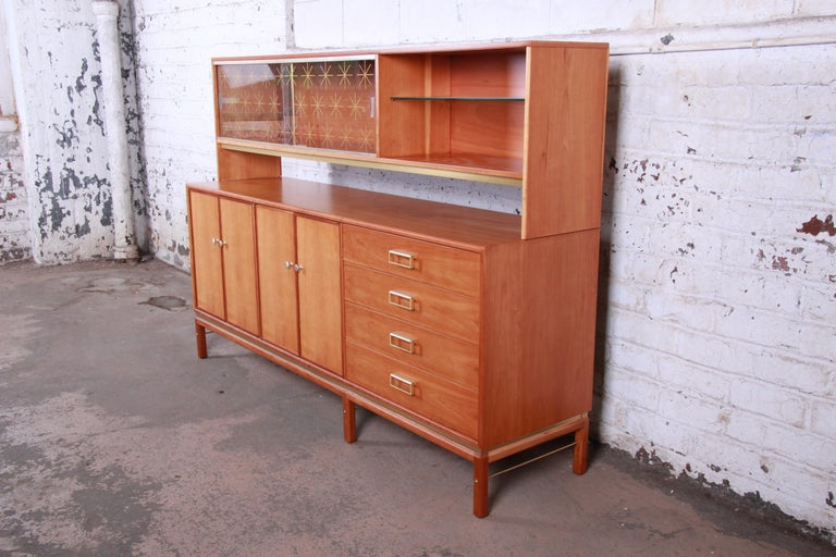 An exceptional Mid-Century Modern sideboard with hutch top designed by Kipp Stewart for his Sun Coast line for Drexel Furniture. The sideboard features stunning cherrywood grain and sleek midcentury design. It offers ample storage, with four