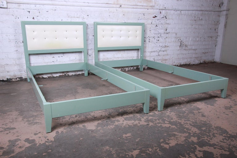 Offering a rare and gorgeous pair of twin beds from the 1940s Mandarin collection by Kittinger. The beds feature solid wood construction with the original duck egg green lacquered finish and tufted Naugahyde headboards. A simple, yet stunning