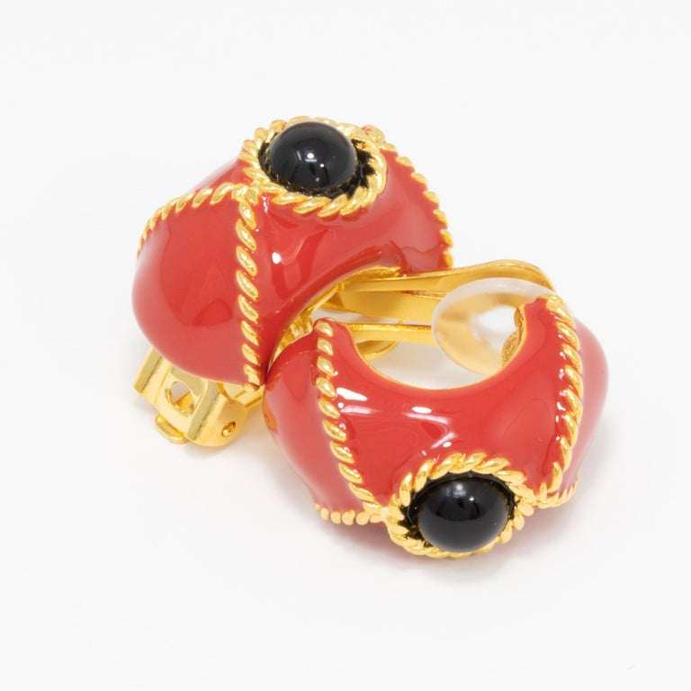 A pair of clip on earrings by Kenneth Jay Lane. Each gold-plated earrings is painted in red enamel, and decorated with a black cabochon centerpiece and gold accents.  Tags, Marks, Hallmarks: KJL, Made in USA