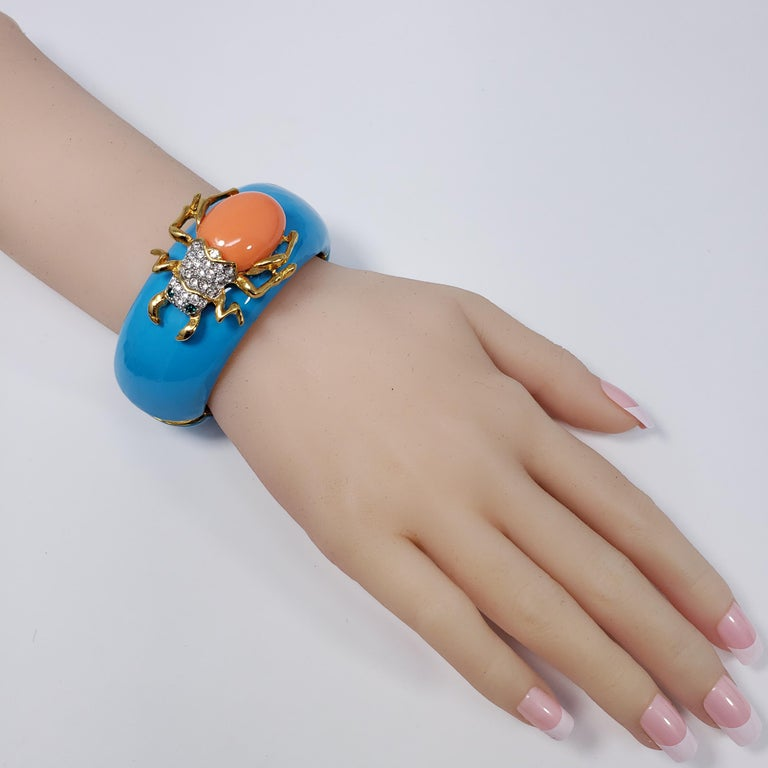 A colorful bracelet by Kenneth Jay Lane! Features a turquoise enamel face accented with a pave-crystal scarab with a resin back.  This bracelet has white enamel marking on one side, a small imperfection.  Inner circumference: 16 cm Diameter at