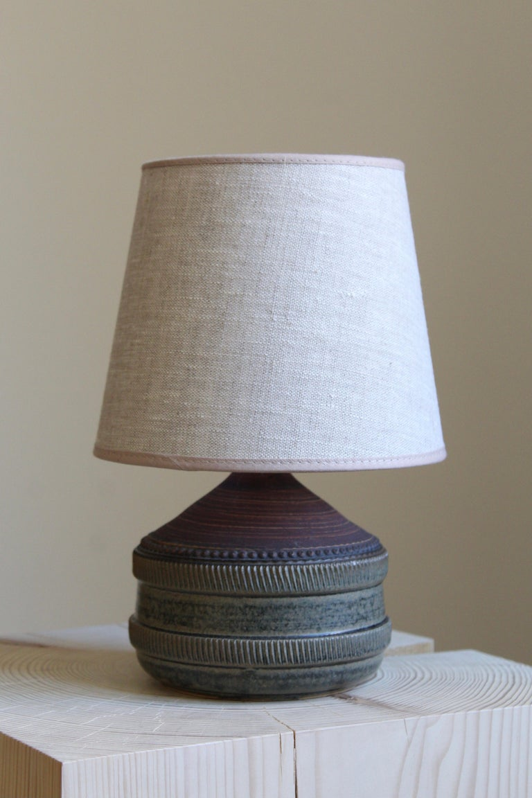 A table lamp by Klase Höganäs. In stoneware. Signed. With brand new high-end linen lampshade.