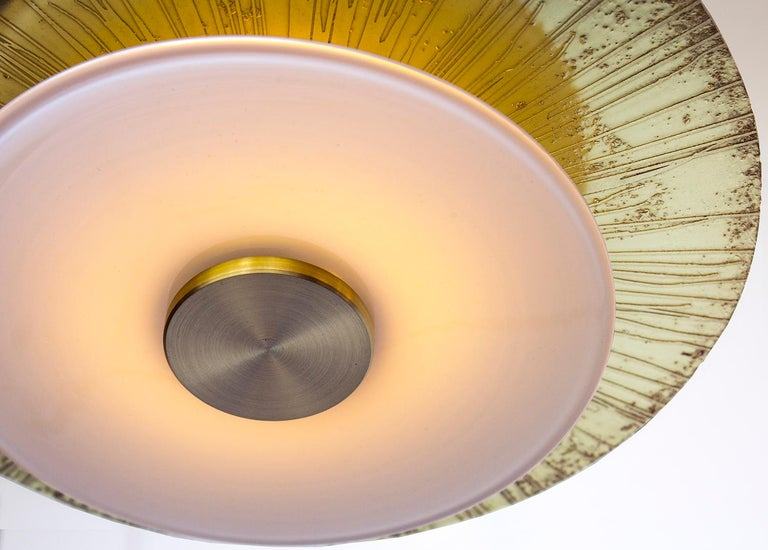 At eleven inches in diameter the Klein pendant embraces a layered light assembly comprising a hand blown white glass rondelle and an etched and polished brass disc. Mounted to a central white light tube, the Klein pendant offers ample up lighting as