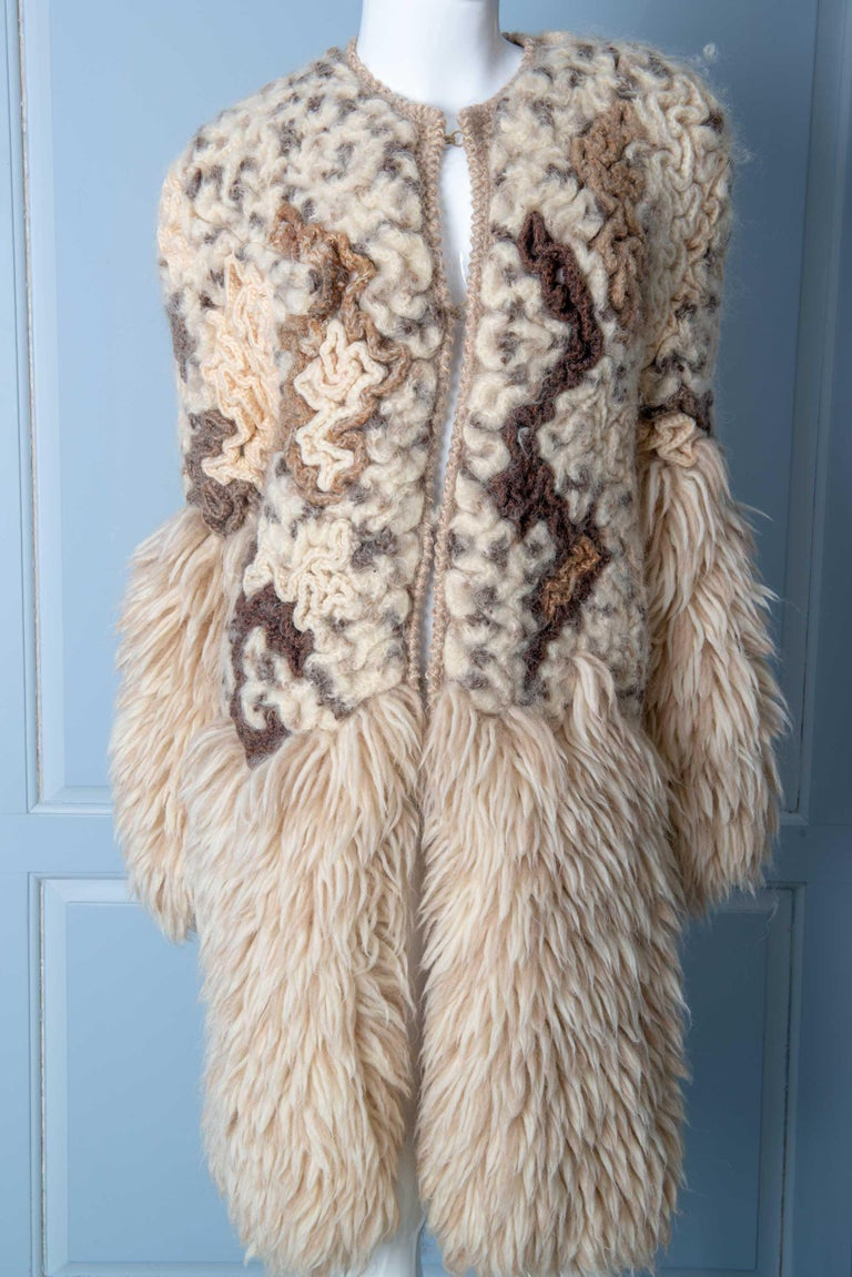 Very unusual knitted coat from the 1970s with a beret. Large hook and eye closures. Exquisite intricate hand knitting.