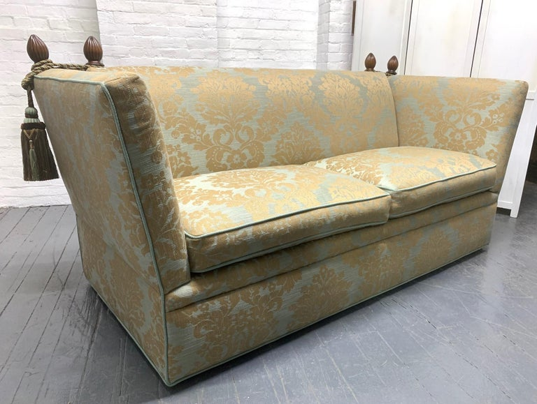 Knole sofa with custom upholstery. The sofa has rope and tassels wrapped around decorative walnut finials with hinged sides.