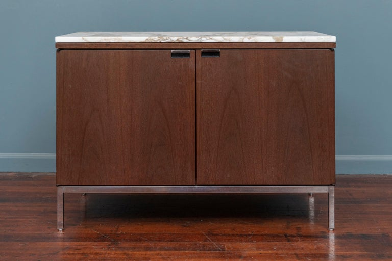 Knoll style marble top walnut two door credenza or cabinet. Having four adjustable shelves and a later added electrical access hole. Supported on a chrome squared frame on adjustable feet. In very good original condition and ready to install, top