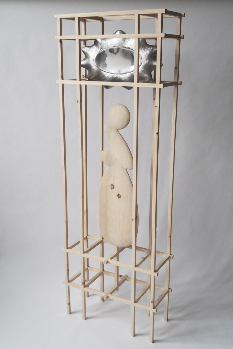Two hammered steel shells, welded, one side polished and housed in a gridded structure of knotty pine wood. The two disparate elements are bridged by a third, a carved pine form completing the composition.