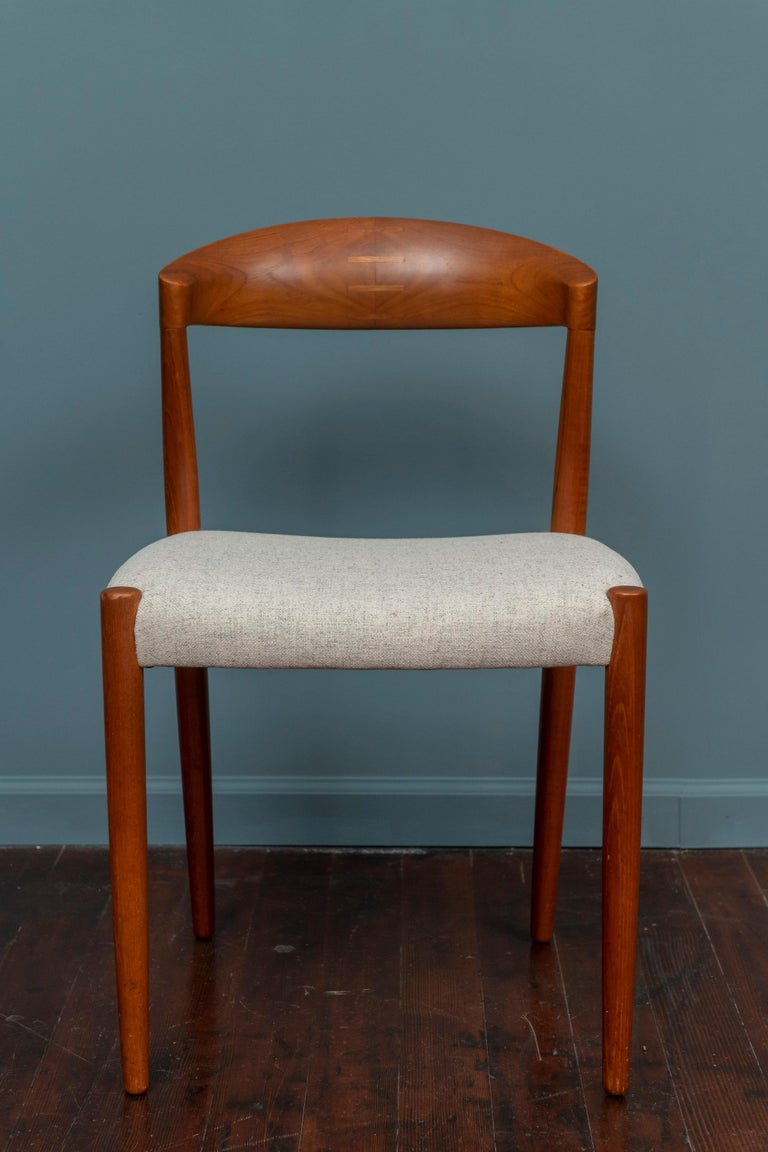 Set of four Danish chairs in teak by Knud Andersen, manufactured in the 1960s. Round shaped backrest with beautiful details, solid constructed with newly upholstered light grey wool seats. In very good condition with a nice and warm patina!