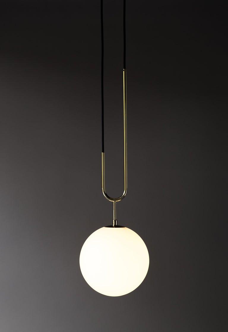 Koko  Drawing inspiration from a pearl pendant, the Koko collection is elegant and modern, with its luminous blown glass and brass arch detail. A versatile light, Koko can be displayed as a single pendant or arranged in a grouping as a