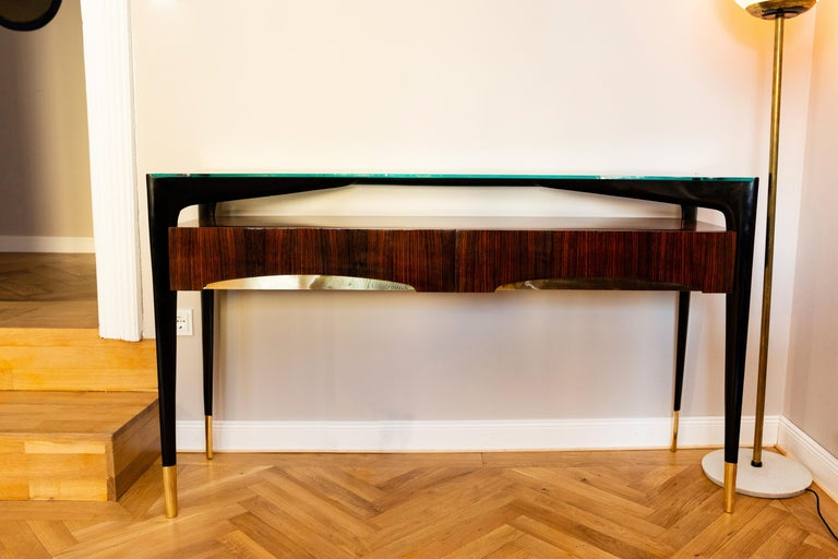 Elegant console, Italy circa 1950, polished Santos rosewood, black shellac polished elegant shaped legs with massive polished brass legs and organically shaped pad, glass top, two front drawers with brass elements. This console is ornate newly