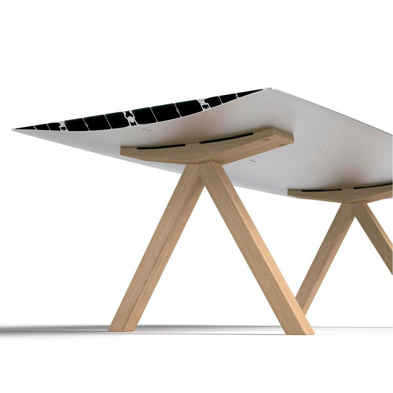Top in bevel edged extruded aluminium. Surface laminated in oak effect. Natural ash wooden legs.