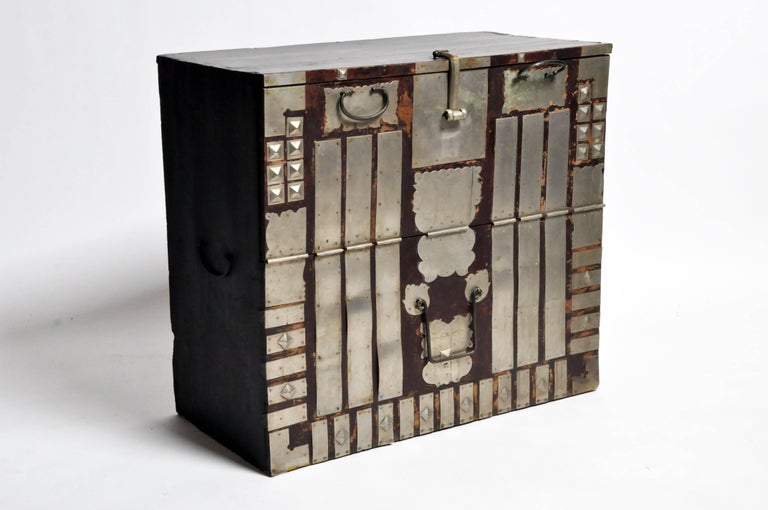 This softwood storage trunk has highly stylized decorative metal fittings, and was used to hold blankets, garments and other gifts that would be presented to the newlyweds as part of the dowry. It has a fall-front opening and large metal handles for