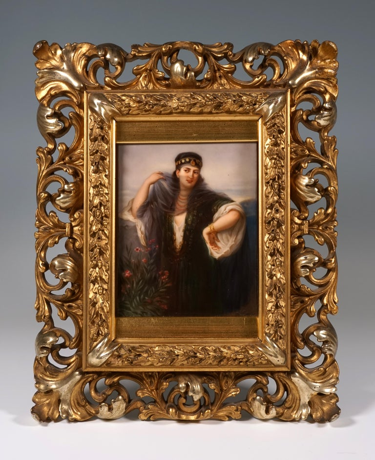 Portrait of a girl in oriental-style clothing with a headdress and veil in a scenic setting. In original, gilded wood frame with acanthus leaf and oak leaf garland carving.  Manufactory: KPM Royal Porcelain Manufactory Berlin, Germany Dating: