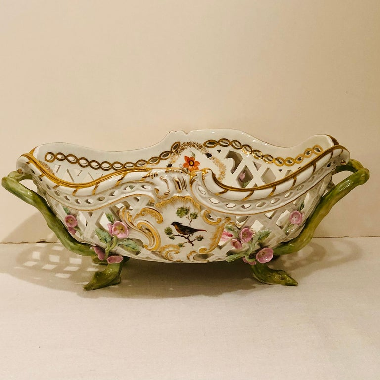 This is a fabulous KPM bowl beautifully decorated with reticulation and raised pink flowers. Each side of the KPM bowl is painted with a different bird painting. The inside of the bowl is painted with five different medallions of flower bouquets as