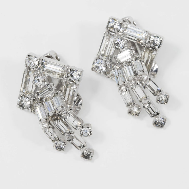 A pair of art-deco inspired dangling clip on earrings, featuring round and baguette cut clear crystals on s silver-tone setting.  Tags, Marks, Hallmarks: Kramer