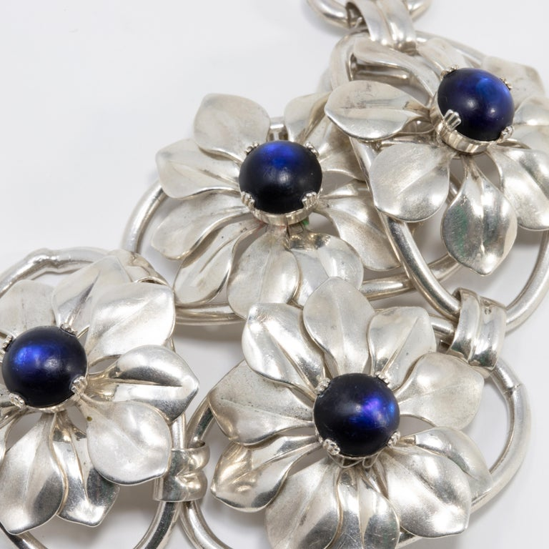 A stylish vintage bracelet. This pretty accessory features four flower links, each with a single dark blue/indigo gemstone. Fastened with a foldover clasp.  Hallmarked: Kreisler Sterling