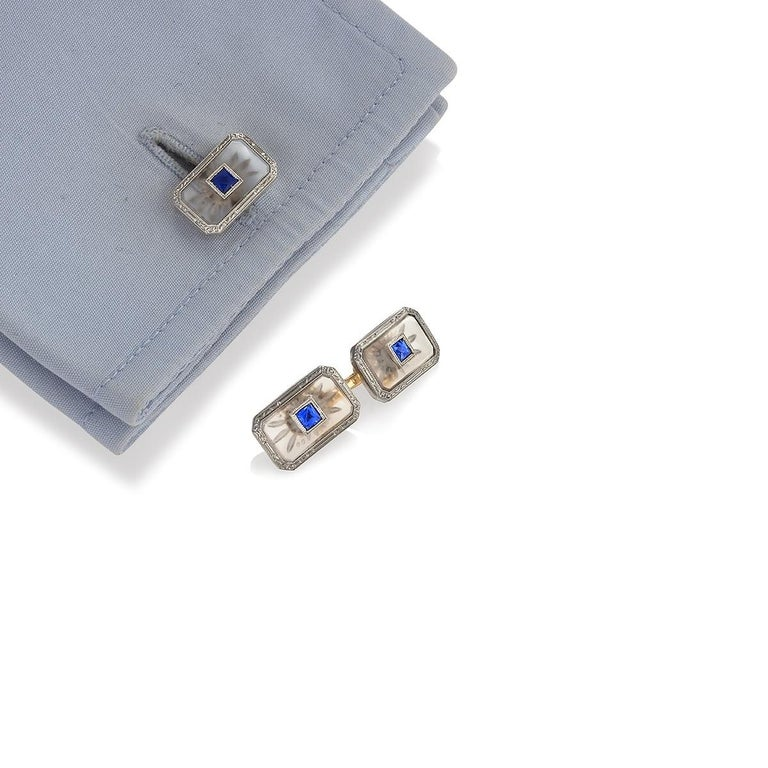 An American Art Deco platinum and 14 karat gold, sapphire and rock crystal dress set by Krementz & Co.  The dress set consists of a pair of double sided rectangular cuff links set with center french-cut sapphires and 4 square dress studs made of