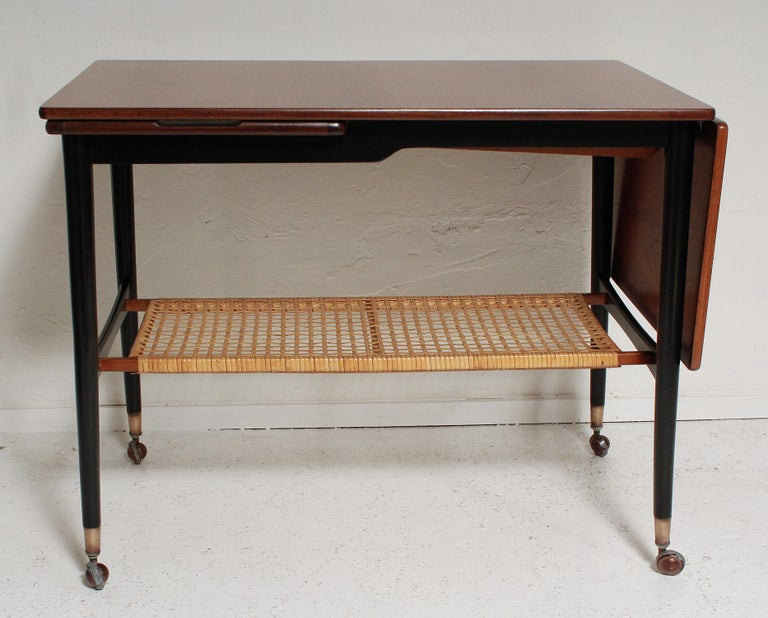 It's a side table, a coffee table, a serving table - it's a beautifully restored Danish walnut and rattan drop-leaf host/Hostess table with slide-out stainless steel serving tray, black painted legs, and brass sabots, by Kresten Buch, circa 1960.