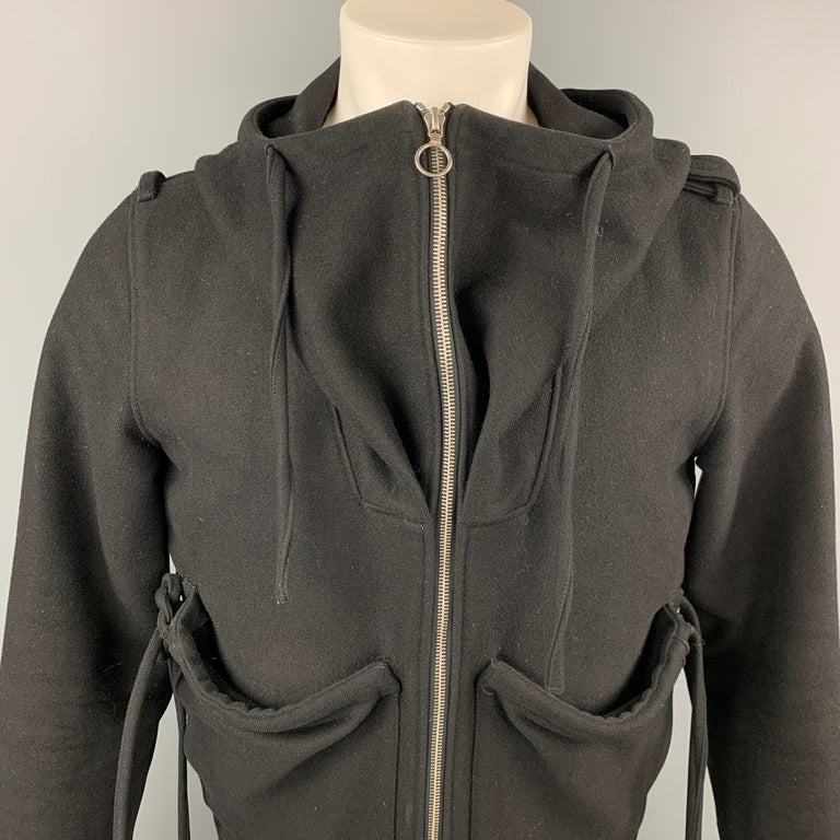 KRIS VAN ASSCHE jacket comes in a black wool blend with a quilted liner featuring hooded style, patch pockets, strap details, zipper sleeves, ribbed hem, epaulettes, and a full zip up closure. Moderate wear.  Good Pre-Owned Condition. Marked: