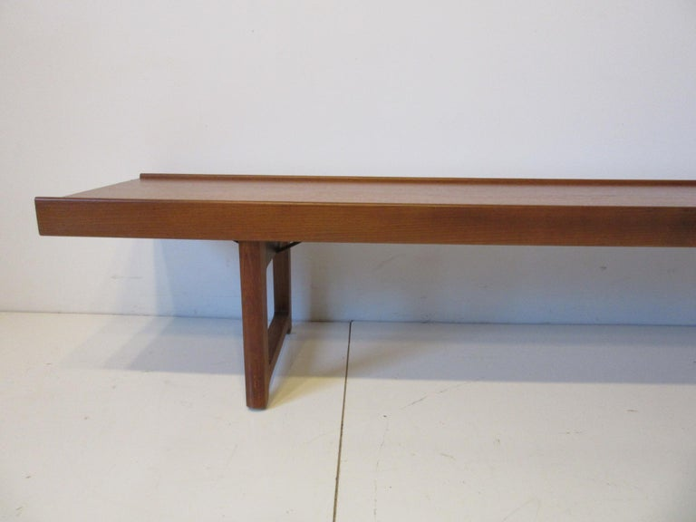 A long solid teak wood Krobo bench with lip to both front and back edges sturdy legs with lower supports this very well crafted bench is perfect for that entrance way or large window area when you need extra seating or just a stylish piece of